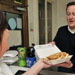 Conservative Party leader David Cameron buys food in a fish and chip shop in Long Town village