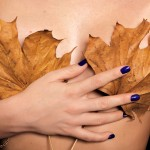 female breasts covered with dry maple leaves