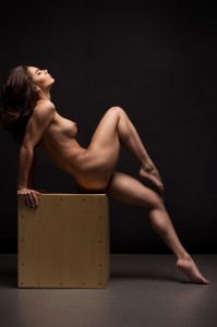 Naked woman Yoga on black background. Fine art photo of female body.