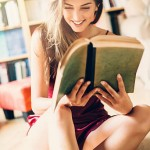 Woman dressed in a sexy lingerie reading a book.