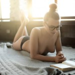 young sexy beauty woman lie home on floor and read book, topless